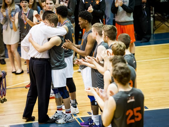 Northeastern head coach Matt Wilson awards medals to players and hugs Matt Schaeffer (10) after the Bobcats won the YAIAA championship in May. The Bobcats will play for their fourth straight state title on Saturday.