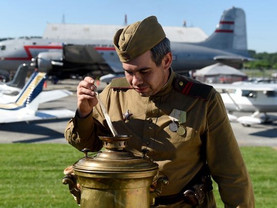 Robert Bell, portraying a WWII-era Soviet infantryman, boils water in a samovar at the York Airport Aviation Days.