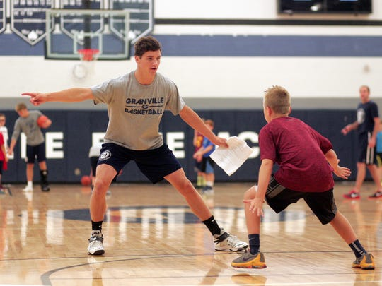 Teddy Parsley runs Granville youth boys basketball camp participants through drills Monday morning.