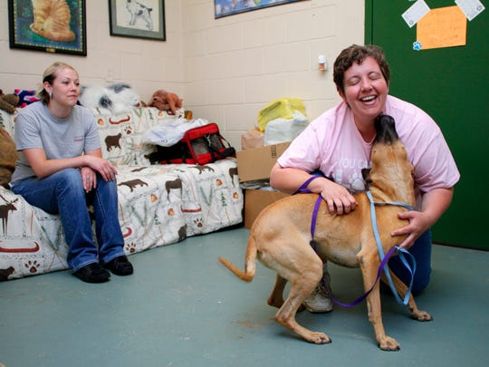 Coshocton County Animal Shelter volunteer Courtney Timmons, left, and rescue coordinator Rachael Selders play with one of the four-legged residents at the shelter.