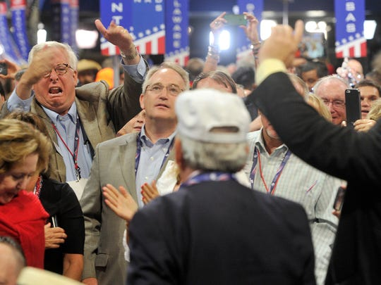 David Johnson, left, a delegate from Ohio reacts to