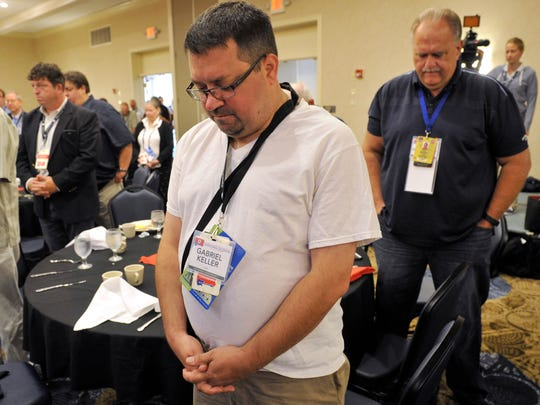 Gabriel Keller, center, joins the room in prayer before the start of the Pennsylvania Republican delegate breakfast in the Westlake, Ohio DoubleTree by Hilton Hotel on Tuesday, July 19, 2016. Keller, of western Pa., is a guest of Matthew Jansen, seen here on the left, who is a Pennsylvania delegate representing the 4th Congressional District at the Republican National Convention.