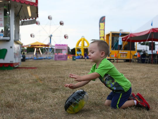 Corbin Vogelsong, 2, plays with a festival prize Thursday