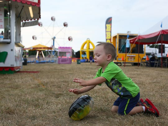 Corbin Vogelsong, 2, plays with a festival prize Thursday evening at the West Lafayette Homecoming Festival.