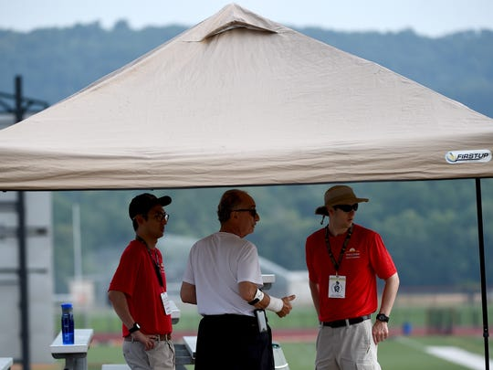 Medical staff with the Keystone State Games Kenneth Lee, left, and Matt Heitzenrater talk to athlete Charles Gentile of West Chester underneath a tent near the tennis courts at Central York High School.