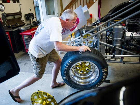 Tim Dietz mounts a front tire on son Chase Dietz's 6d sprint car while working in their garage on Thursday, July 28, 2016.
