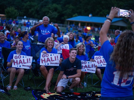 Chase Flickinger, center, brother of Hali Flickinger, poses for a photo taken by his girlfriend Courtney Knotts of the crowd gathered to watch Hali compete in an Olympic semifinal swim during an outdoor party at Spring Grove Community Park on Tuesday, Aug. 9, 2016.