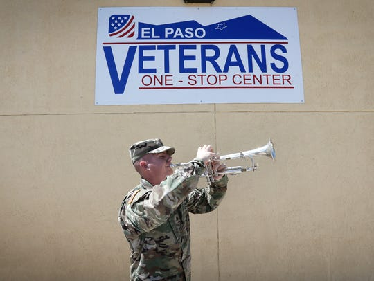 A soldier plays taps outside the El Paso Veterans One