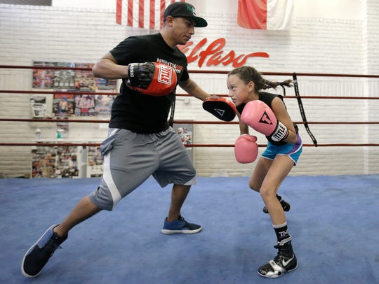 Ivy Enriquez, 9, works out with her father, Sergio