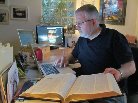 Author Chris Stepien of Dearborn works in his office.