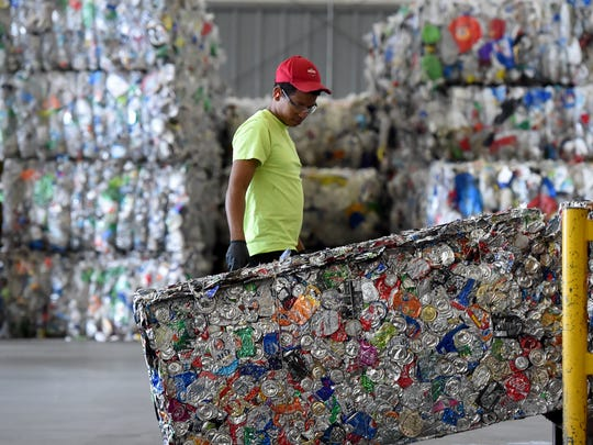 A worker clears non-aluminum items from a  bale of crushed cans at Penn Waste's recycling plant in Manchester Township.