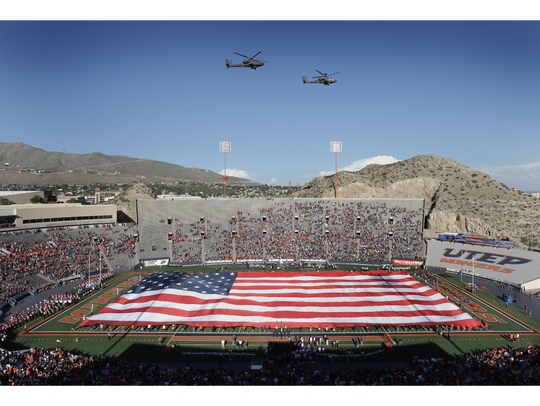 A pair of Blackhawk helicopters provide a flyover as a giant flag covers the field prior to the UTEP's vs. Army game.