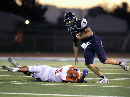 Del Valle quarterback Raymond Montez pushes Canutillo defensive back to the turf to avoid the tackle as he rolls out of the backfield Friday.
