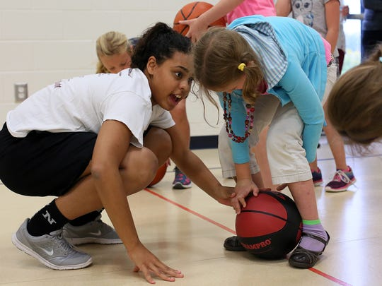 Natazia Thomas, left, instructs Legend Elementary students Wednesday after school during a clinic at Legend Elementary hosted by The Newark High School girls basketball team.