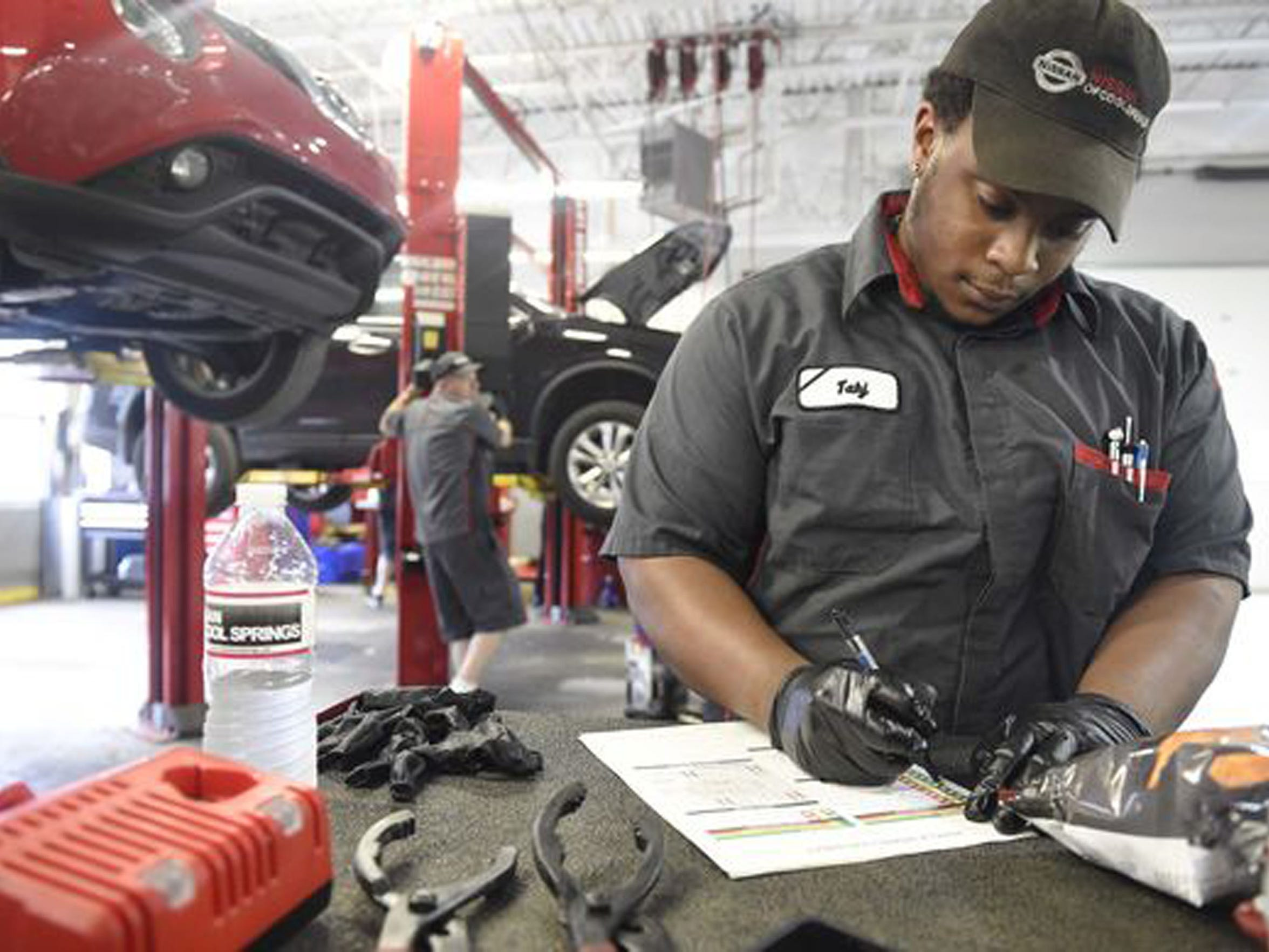 Tennessee Promise student Tahj Turnley fills out paperwork while servicing a car at the Nissan dealership in Cool Springs. He attends the Tennessee College of Applied Technology Hohenwald campus in Spring Hill.