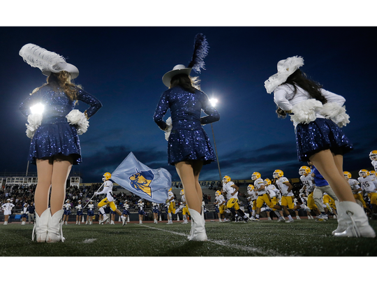 The Eastwood football team take the field past a row of Trooperettes Friday at Coronado High School.