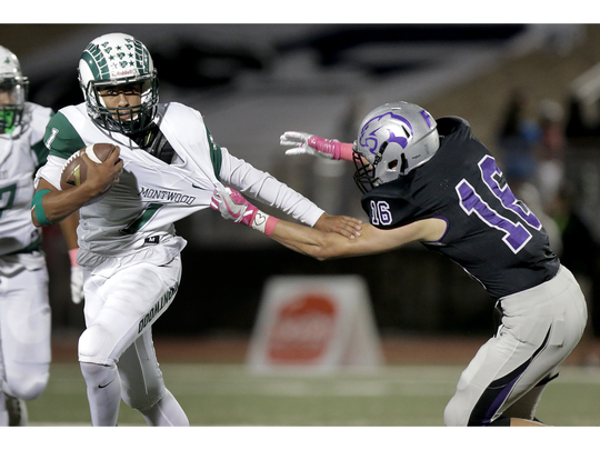 Montwood quarterack Andrew Fernandez takes off on a keeper as Franklin linebacker Kaleb Gutierrez tries to drag him down by his jersey Friday night at Franklin High School. Montwood beat the Cougars 56-48.