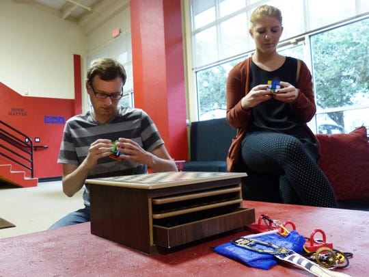 Reporters Tad Mast and Shelby Reynolds attempt to solve plastic puzzles on Oct. 12, 2016 before entering the 'Dinner Party' room, which is one of five rooms inside Breakout Escape Room Bonita. The interactive attraction allows participants the chance to escape from a locked room within 60 minutes.