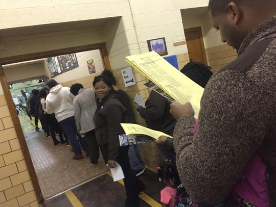 Voters look over a mock ballot as they stand in line