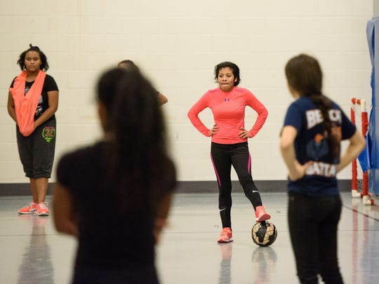 Junior Michelle Molina rests her foot on a ball during a break in a team passing exercise at William Penn High School on Dec. 14. Girls' soccer was re-introduced to the school this fall on the junior varsity level.