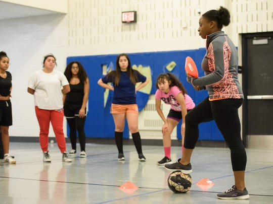 Coach Alexis Lindo, right, gives directions for a passing drill to girls during a workout for the William Penn High School soccer team on Wednesday, Dec. 14, 2016. The school is planning to reintroduce several sports, including boys and girls soccer.