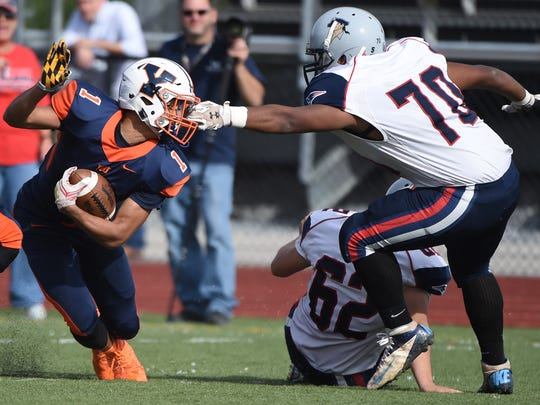 Dayjure Stewart, left, looks to wiggle free from the New Oxford defense during a game last year at Small Field. William Penn won 62-29. It was the program's first victory in two years.