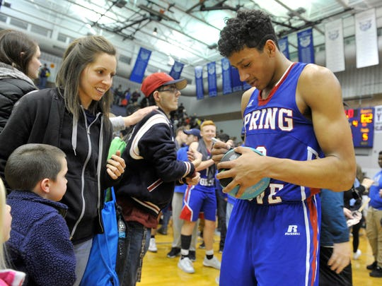 Spring Grove's Eli Brooks signs an autograph for 5-year-old Owen Seibert following the Rockets' 62-58 victory on Tuesday, Jan. 31, 2017.