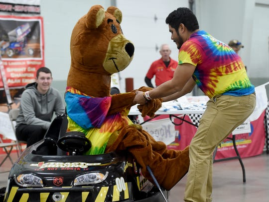 Hickory the Bear, with Hickory Falls Entertainment Center, gets a hand from Chris Villeda after the mascot fell into a kiddie car during the Racing Xtravaganza at the York Expo Center on Saturday, Feb. 4, 2017.