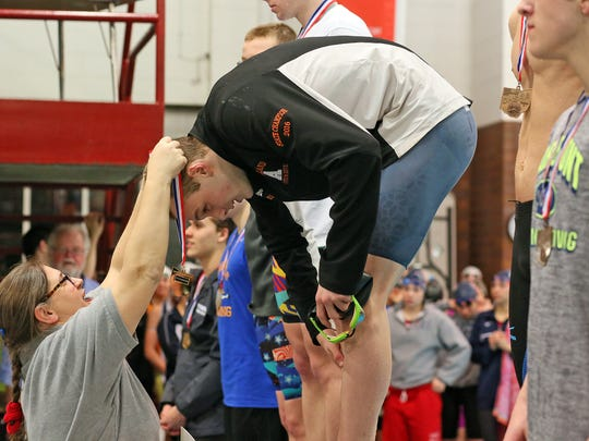 Ashland junior Hudson McDaniel receives his first-place medal after repeating as a state swim champ in the 100-yard breaststroke.
