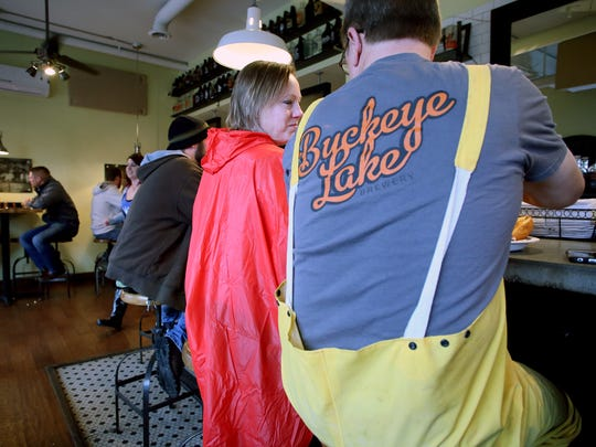 Denise and Doug Soma, of Millersport, dine at Buckeye Lake Brewery Wednesday evening where lake supporters celebrated the closing of the spillway. Customers dawned raincoats hoping the lake will fill in time for boating season.