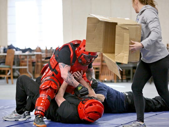 Newark Police Officer April Hunt pulls the box from over Detective Todd Brunton's head as Officer Jerad Angle and Detective Todd Green assault Brunton Wednesday during defensive tactics training.