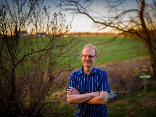 Mark Allen, a 20-year resident of Manchester Township, fears a sports complex proposed to be built on farmland (at left) adjacent to his yard will negatively impact his neighborhood with traffic and stormwater drainage issues. A drainage ditch currently separates the field from his property line, where Allen enjoys the summer views of corn from a wooden chair in his garden, right.