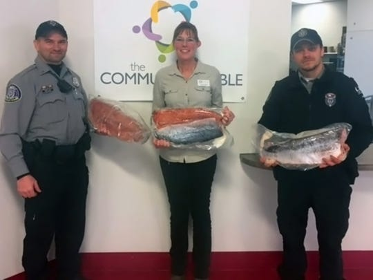 Lt. Jeremy Peery (left), Warden Kevin Christorf (right) are pictured with manager Lois Salinas of the nonprofit Community Table in Eau Claire. The two wardens, who serve the Lower Chippewa Warden Team, recently delivered 500 pounds of donated processed salmon and panfish fillets to the facility. The donation is part of the state policy when it comes to donations of confiscated fish.