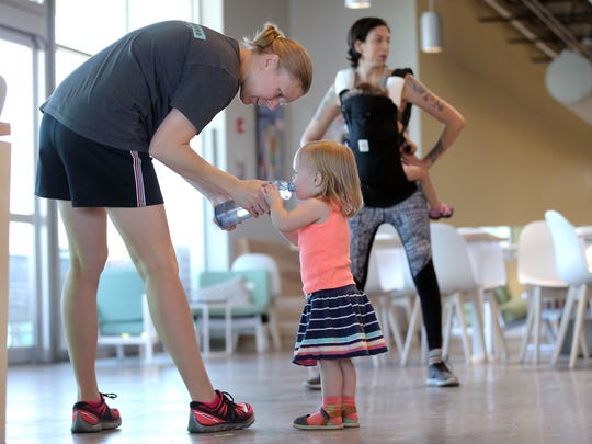 Kristyn Ingram shares her water with her daughter Ada Rose, 2, during her exercise class Wednesday at Whole Foods in west El Paso.