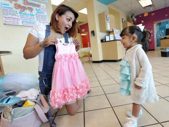 Paola Marquez shows her daughter a dress she bought