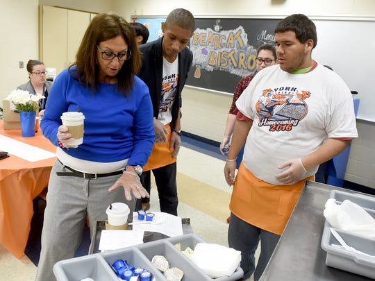 Michelle Masco, a Life Skills Support teacher at William Penn High School, directs students Isaac Hughes, right, and Chamber Weatley on where to deliver food during the first day of the Bearcat Bistro on Thursday, May 4, 2017. The bistro, set up by Masco, was created to help give special needs students life skills she hopes they can take beyond the walls of the school.