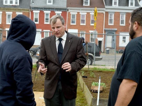York City Council President Michael Helfrich, who is running for mayor, talks to voters in the neighborhood along Walnut and Broad streets.