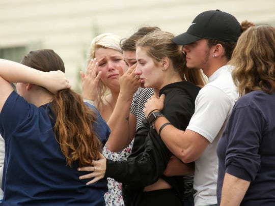 Friends and relatives of victims console each other in May 2017 outside of Pine Kirk Care Center on Main Street in Kirkersville. A gunman killed Kirkersville Police Chief Steven Eric DiSario, two Pine Kirk Care Center employees, and himself.