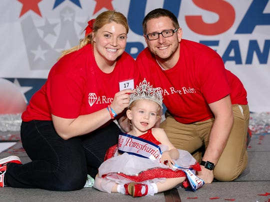 Submitted photograph of  Mindy and David Hoffman, rear with their daughter Ruby, who was crowned the Tiny Toddler a the East Coast USA Beauty Pageant. The 2-year-old from West Manchester Township is living with the rare brain disease H-ABC, or Hypomyelination with atrophy of basal ganglia and cerebellum.