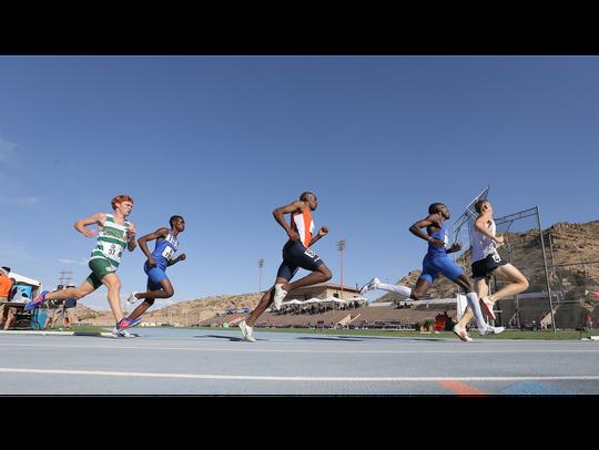 Runners in the men's 1500 meter prelim round the corner