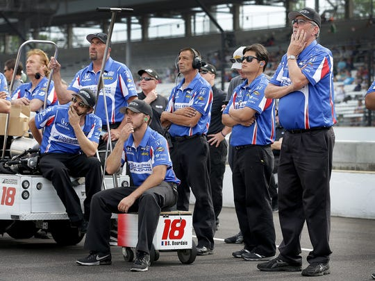 The crew of Dale Coyne Racing IndyCar driver Sebastien Bourdais (18) watch the video board as the EMS crews work to free him from his car following his crash during qualifying for the Indianapolis 500 Friday, May 20, 2017, afternoon at the Indianapolis Motor Speedway.
