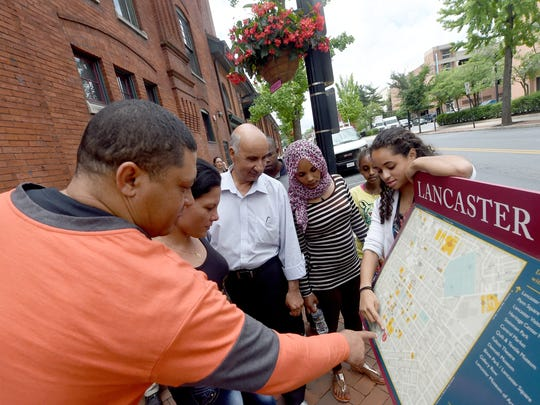 Dominique Cressler, right, a teacher with Church World Service, challenges her class of ESL students from St. Mary's Church, to find locations on the map of Lancaster city as they walk the streets of downtown Lancaster to practice their english.