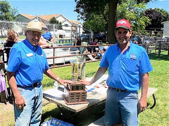Long time fair board member Merton Breunig (52 years) and dairy superintendent Dave Endres and the Breunig family sponsored Dairy Showman trophy.