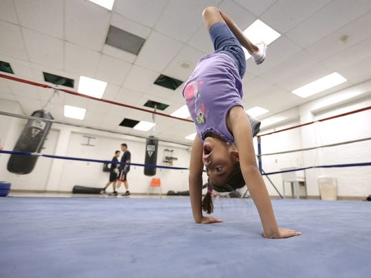 Shae Delgado gets in a little gymnastics practice in the ring before her father Herman Delgado starts training his boxers at the Armijo Recreation Center.