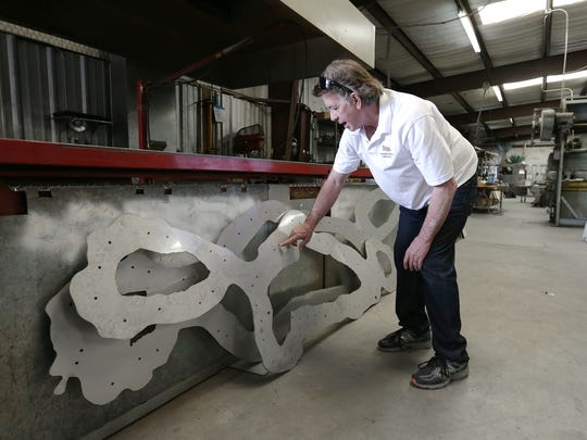 "Tim Downing, owner of Industrial Stainless International, shows what a slice of the sculpture ""Run"" looked like before being put together."