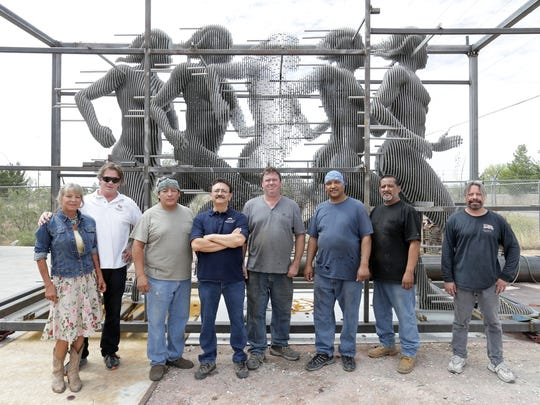 "Monica Downing and Tim Downing and the crew at Industrial Steel International in Chaparral, N.M., stand by ""Run,"" a sculpture that will be placed at Texas Tech University's Sports Performance Center in Lubbock. The company built the 12-foot-high sculpture that will stand on a 6-foot-tall platform."