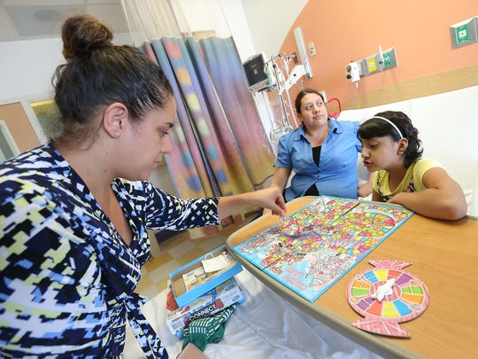 Immigration attorney Linda Rivas, left, plays Candy Land with Alia Escobedo, 8, in her hospital bed at El Paso Children's Hospital. Rivas is trying to get Maria Elena de Loera, center, Alia's mother, to stay in the United States while her daughter undergoes treatment for small cell osteosarcoma.