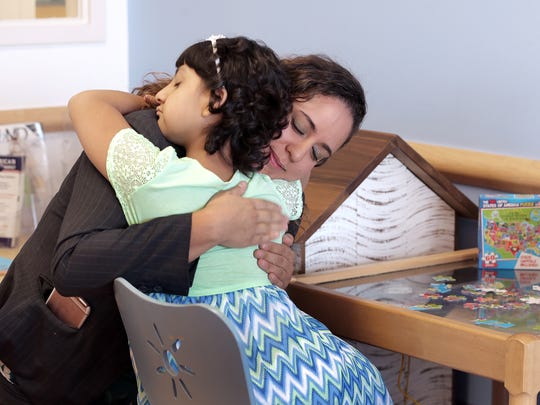 Alia Escobedo hugs her mother's immigration attorney, Linda Rivas, after learning her mother was granted a six-month stay in the United States. Alia is undergoing cancer treatments at El Paso Children's Hospital and wants her mother by her side.