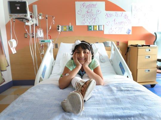 Alia Escobedo is all smiles in her room at El Paso Children's Hospital on the day her mother was granted a six-month stay in the United States.