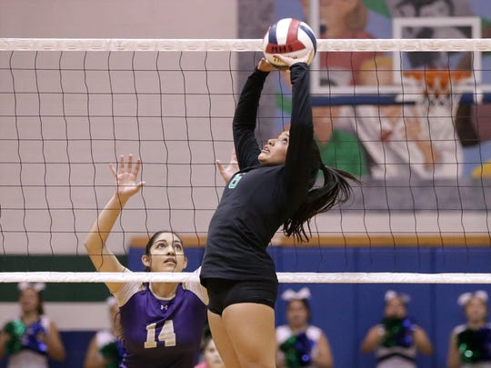 Montwood setter Cassidy Sanchez jump sets while covered by Burges's Andrea Gandarilla during a match earlier in the season